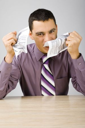 irritable: Angry man at the desk crumpling two sheets of paper. (papers form is copyright free)