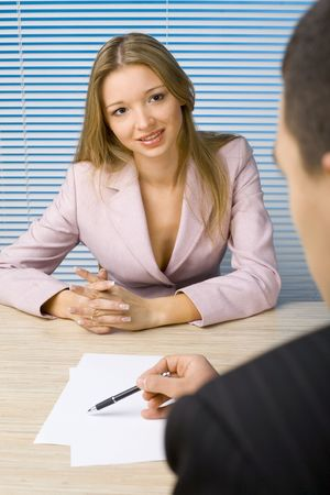 to clarify: Woman and man at the office desk. Mans writting something - only his hands visable. Womans talking or smiling.
