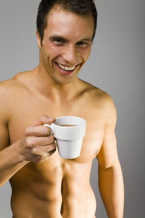Young man standing nacked with cup of tea/coffee next to the window. Stock Photo - 770735