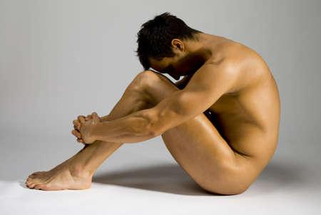 uomini nudi: Giovane uomo seduto e muscolare. Ha il viso di nascondere in ombra.  Archivio Fotografico