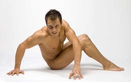 Young and muscular man sitting. Hes face looks wild.