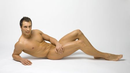 erotic male: Young and muscular man lying on the grey background in the studio.