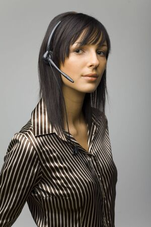 Young woman with telephone headset, isolated on grey background in studio photo
