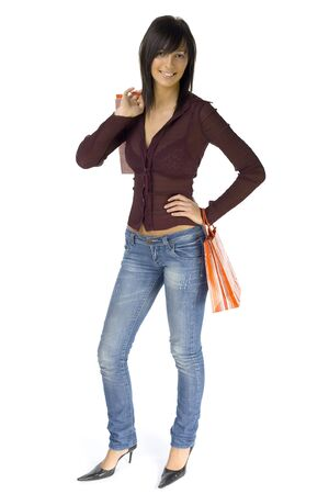 restfulness: Young woman standing with shopping paper bags. Whole body isolated on white in studio. Stock Photo
