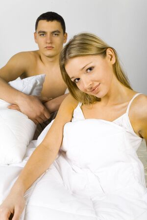 virginity: Young couple in the bed. Both looking at the camera.