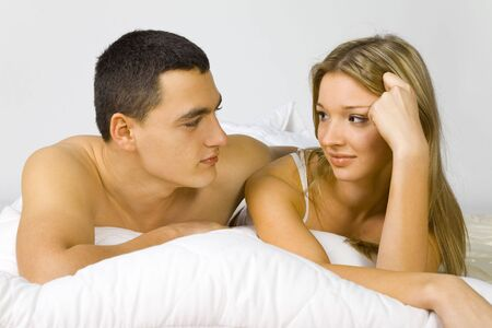 virginity: Young couple in the bed. Mans holding woman. Theyre looking their faces.