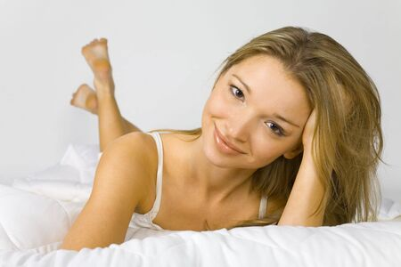 virginity: Young attractive woman lying on white bedding and smiles.