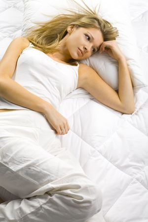 virginity: Young blonde woman lying alone in the bed. Looks dreamy.