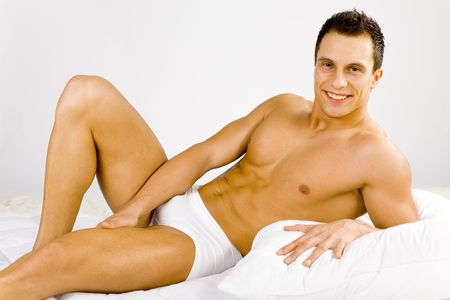 Smiled and happy man lying on the bed. White background in studio.
