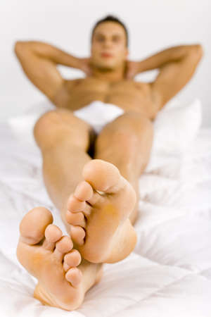 Man lying on the bed. Focus on this foots. Face and rest of body unfocus. White background in studio. Stock Photo - 775264