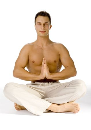 Young attractive man sitting yoga style. Hes eyes closed. White background in studio.