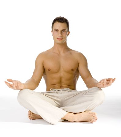 Young attractive man sitting yoga style.  White background in studio.