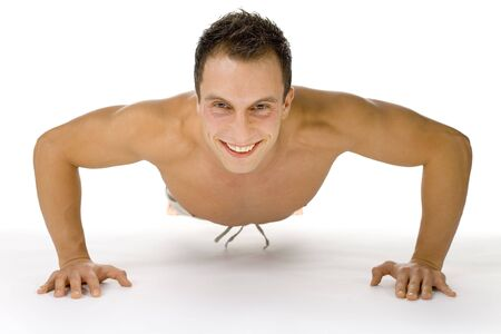 Young happy man doing push up exercise. White background in studio. Stock Photo
