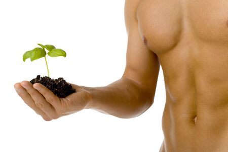 testosterone: Muscular man holding small plant and soil in his hand. Isolated on white in studio.