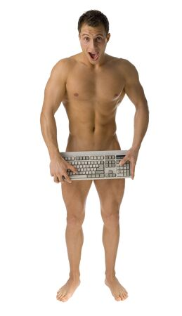 Young athletic man standing naked. Hes hiding his body by computer keyboard. Looks shocked. Isolated on white in studio. Stock Photo