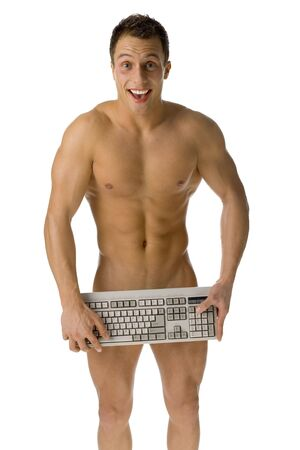 Young athletic man standing naked. Hes hiding his body by computer keyboard. Looks happy. Isolated on white in studio.