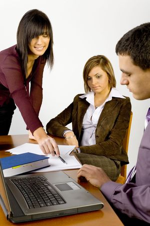 Women and a man having conversation at conferences table. Standing womans  showing something on the paper. Stock Photo