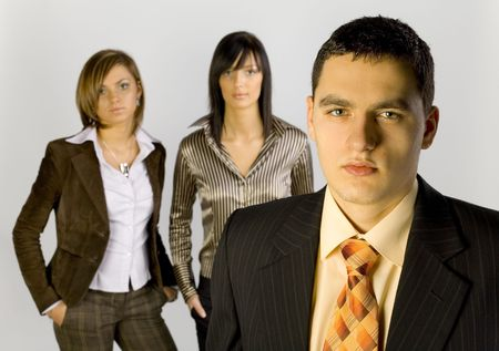 Two women and a man are standing and looking at the camera. There's man-leader at the front of group. Horizontal. photo