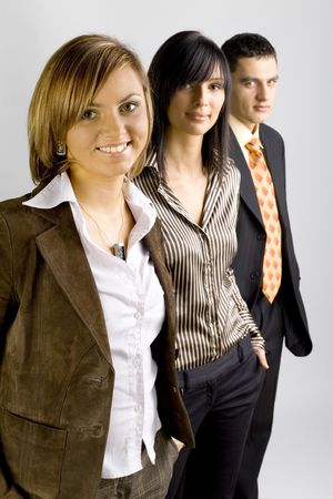 Two women and a man are standing, looking at the camera and smiling. Focus is on the first person. photo