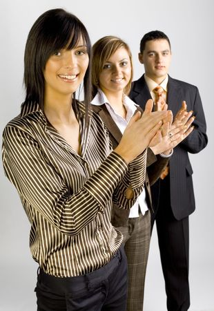 Two women and a man are standing, looking at the camera and clapping hands. Focus is on the first person.