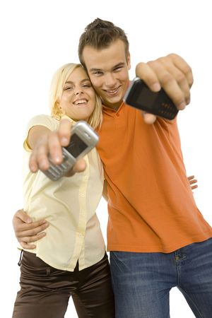 Happy young man and woman are showing mobiles screen to the camera. Isolated on white background in studio. photo