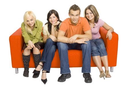 Three young woman and a man are sitting on the orange couch. Theyre looking at the camera. Isolated on white in studio.