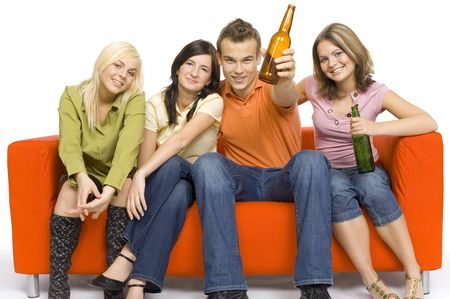 Three young woman and a man are sitting on the orange couch. Two of them are holding beer. Mans making toast.