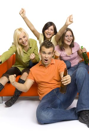 Three young woman and a man are sitting on (and next to) the orange couch. Two of them are holding beer. Theyre shouting and gesturing.