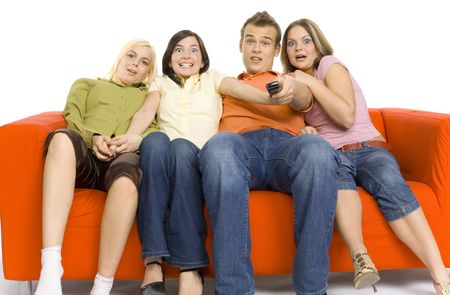 terrifying: Three young woman and a man are sitting on the orange couch and looks like watching TV. Man is holding remote control. There looks terrified.