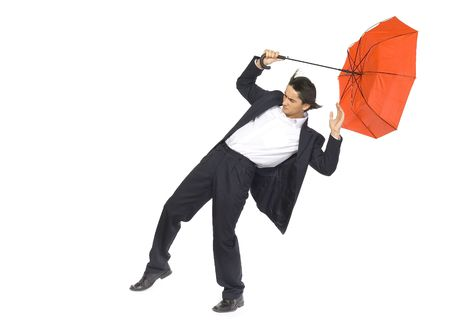 Young man with red umbrella in hand fighting with strong wind blowing on him. Isolated on white in studio.