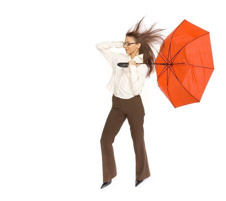 彼女に吹く強い風と戦って手に赤い傘を持つ若い女性。スタジオで白で隔離。