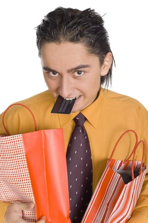 Mans carrying two paper bags. Hes holding credit card by his teeth. Isolated on white in studio. photo