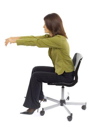 Formalwear 여자의 회전의 자에 앉아입니다. 그녀는 컴퓨터의 키보드에서 타이핑하는 것처럼 보입니다. 스튜디오에서 흰색에 격리. 스톡 콘텐츠