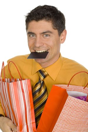 Happy mans carrying two paper bags. Hes holding credit card by his teeth. Isolated on white in studio. photo
