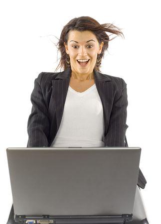 viento soplando: Sentada de los woman de Formalwear con la computadora port�til en sus rodillas. Viento fuerte de There que sopla de la pantalla de los computer. Aislado en blanco en estudio. Foto de archivo
