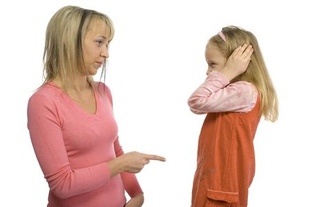 Mother is disciplining her 5-6yo daughter. Girls stopping her ears. Side view. Isolated on white in studio.
