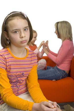 ungeliebt: Sad 10-12yo M�dchen. Konzentrieren Sie sich auf ihr Gesicht. Es gibt ihrer Mutter und ihrem j�ngeren Schwester hinter ihr. Girl's Gef�hl abgelehnt und allein.