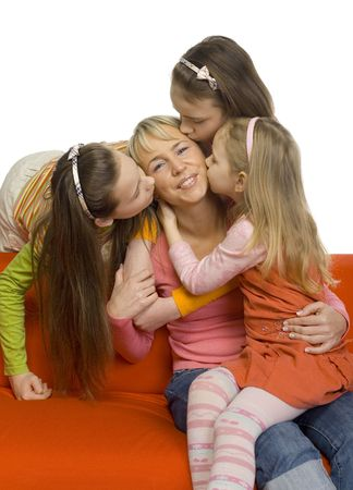 minor: Mother is kissing by her 3 daughters. Mother is sitting on orange couch. Shes smiling and looking at camera. Stock Photo