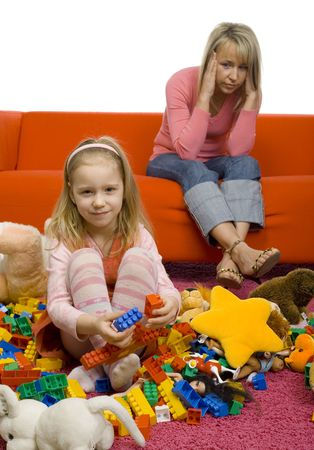 5-6yo girl with her toys on the floor. Theres huge mess. Theres mother sitting on couch behind girl. Mother has headache cause this mess. Stock Photo