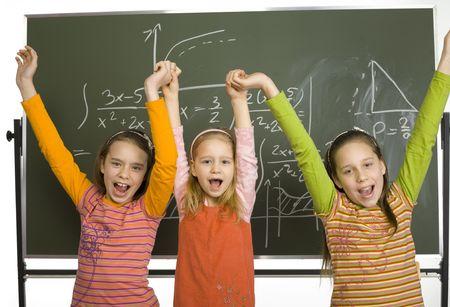 minors: Grupo de ni�as (5, 11 y 13yo) est�n de pie y mirando a c�mara. Se trata de la celebraci�n de las manos en alto y gritando triunfalmente. Detr�s de ellos hay greenboard con las matem�ticas.  Foto de archivo