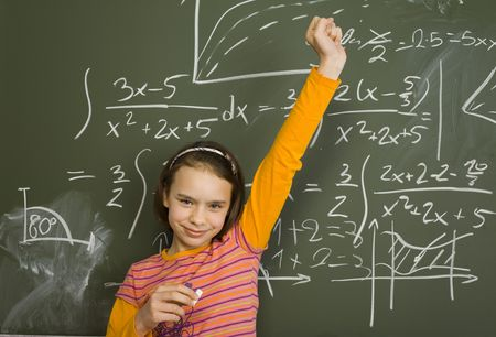 11yo girl are standing with chalk in hand. Shes holding one arm triumphantly up. Behind her theres greenboard with maths. Stock Photo