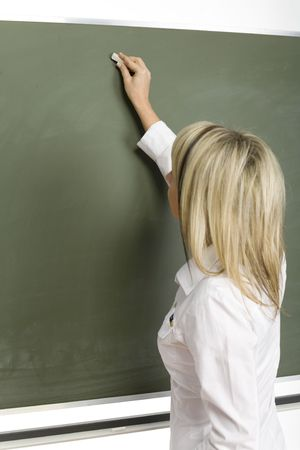 Woman (teachear) are standing with chalk in hand close to greenboard. Shes starting to write. Focus on boardhand.