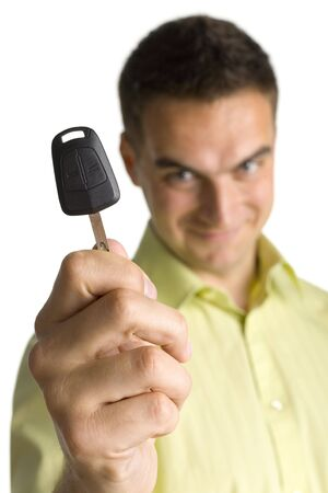 crafty: Smiling young man showing car key. Closeup on key.  Stock Photo