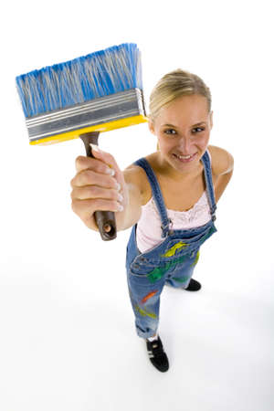blotchy: Young smiling blonde wearing dungarees with paintbrush in hand. looking at camera, headshot, white background. Stock Photo