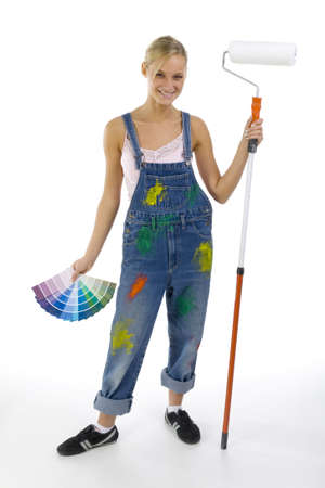 Young smiling blonde wearing dungarees. White background, looking at camera. Whole body Stock Photo