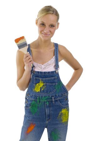 blotchy: Young smiling blonde wearing dungarees with paint brush in hand. Isolated on white in studio. Looking at camera, front side