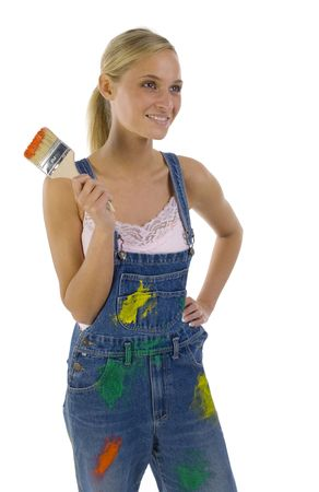 Young smiling blonde wearing dungarees with paint brush in hand. Isolated on white in studio Stock Photo - 957667