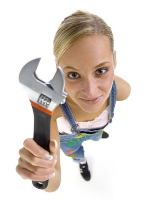 Young smiling blonde wearing dungarees with spanner in hand. Isolated on white in studio. Looking at camera. Whole bod, headshot