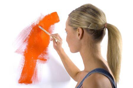 hand schilderen: Jonge blonde met penseel in de hand. Schilderij een muur. Witte achtergrond, achteraanzicht