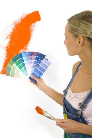 dungarees: Young blonde wearing dungarees with color palettes in one hand and paintbrush on other. Choosing the right color. White background